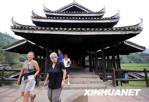 外国游客在游览侗族风雨桥.广西三江侗族自治县独特的侗族建筑和
