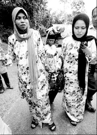 卡蒂卡(左)在鞭刑执行日期延期后,24日与妹妹一起步行回到父亲住