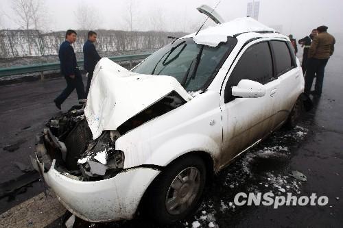 图为现场处理事故的交警提醒过往车辆开启应急灯,小心驾驶。中新社发 刘新 摄 3月16日,由于道路湿滑及大雾天气,新疆乌鲁木齐机场高速路多个路段发生连环车祸。据现场目击者介绍,现场至少有15至20辆车相撞,7人受伤。