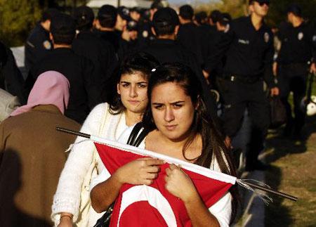 图文:两名少女捧着国旗从防暴警察身边走过