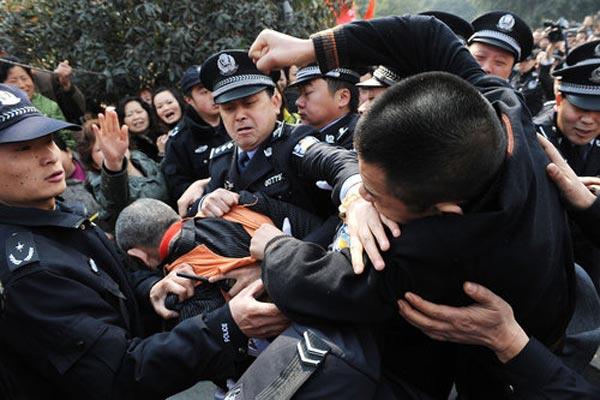 2009年2月23日,成都青羊区公判大会现场,一名愤怒的家长冲破重围,挥拳打向人贩子。