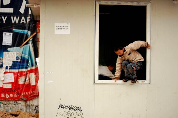 """2009年3月19日19时42分,位于重庆市高新区石桥铺的某驻渝部队营房哨兵遭歹徒持枪袭击,哨兵经抢救无效身亡,歹徒抢走自动步枪一支。警方根据现已掌握的现场情况,已将此案列入反恐打击范畴。虽然发生军人被杀、武器被抢的罕见案件,2009年3月22日,重庆市整体平静,除案发现场周围之外,市区也没有出现特别多的警察,市民工作和生活秩序正常。案发现场周围处于闹市区,市民仍正常在进行经济交易活动,丝毫未受案件的影响,周围市民也没有产生恐慌情绪。据当地一名不愿透露姓名的摊贩介绍,因案件的震惊程度,近几天案发现场周围出现许多陌生人,这些陌生人有的是记者,有的是穿着便衣的警察。当地人都尽量减少与陌生人的会话,生怕惹上麻烦。<来源:人民图片网>图为2009年3月22日,重庆市石桥铺""""歹徒枪杀哨兵""""案发现场周围,孩子正在玩耍,称对枪杀的事毫不知情。"""