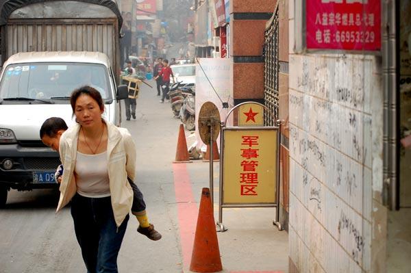 """2009年3月22日,重庆市石桥铺""""歹徒枪杀哨兵""""案发现场周围,市民正在从军事管理区走过。"""