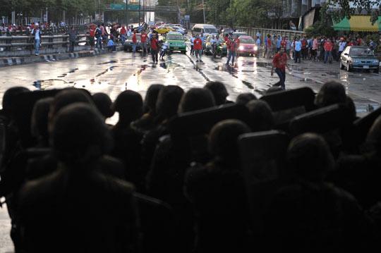 """泰国总理阿披实12日宣布在曼谷等地实施紧急状态法后,大批士兵乘坐军车和坦克进入曼谷,把守50多处交通要点。但""""红衫军""""成员随后夺取了一些重要据点..."""