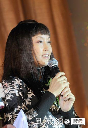 刘晓庆穿着一件中国风的花袄,长发披肩,用齐刘海遮住额头的皱纹,她