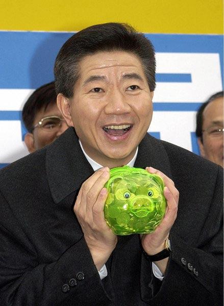 2002年11月29日,韩国新千年民主党总统候选人卢武铉手持一个储蓄盒与支持者见面