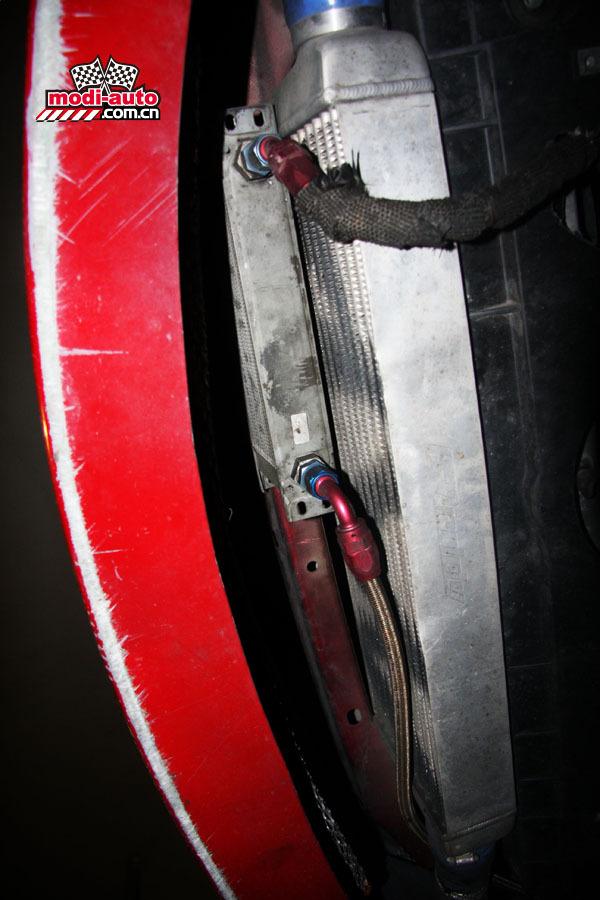 引擎现已不使用三元催化转换器,一是降低涡轮背压,也有助快速排走高温。但氧传感器的信号需要处理一下,不然引擎故障灯会亮。在这里,店家使用的是电阻法。后面的排气管径全部是63mm的不锈钢,仅TRUST尾段有一个消声器,尽管如此,这部车的排气声属于可以接受的一类。  三元催化转换器已被拆除,氧传感器的信号也被处理过才能过得了原装ECU一关。  TRUST尾鼓。  机油冷却器以外,马六还有一个大水箱帮助降温。